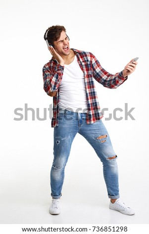 Full length portrait of a cheerful attractive man in headphones enjoys listening to music while standing and singing isolated over white background stock photo