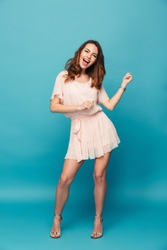 Full length portrait of a cheerful beautiful girl wearing dress having fun and dancing isolated over blue background