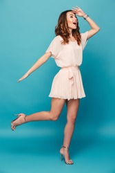 Full length portrait of a cheerful beautiful girl wearing dress looking far away isolated over blue background