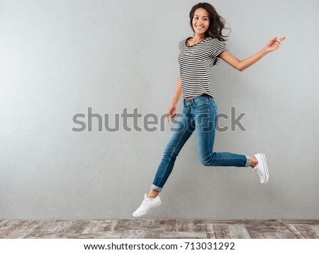 Full length portrait of a cheerful casual asian woman jumping isolated over gray background