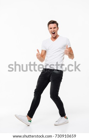 Full length portrait of a cheerful excited man in white t-shirt standing and showing thumbs up gesture with two hands isolated over white background
