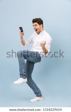 Full length portrait of a cheerful handsome young man standing isolated over blue background, holding mobile phone, celebrating