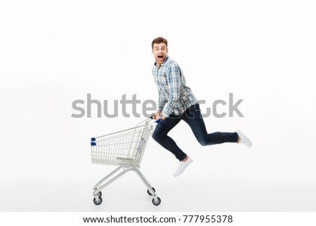 Full length portrait of a cheerful man jumping with a shopping trolley isolated over white background