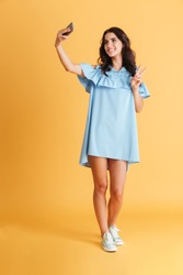 Full length portrait of a cheerful smiling woman in blue dress taking selfie and showing victory sign isolated on a orange background