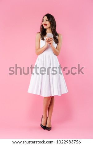 Stock Photo Full length portrait of a cheerful young asian woman dressed in white dress holding mobile phone and looking away isolated over pink background