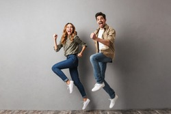 Full length portrait of a cheerful young couple jumping together and celebrating success isolated over gray