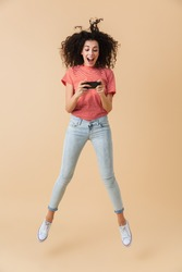 Full length portrait of a cheerful young girl playing games on mobile phone while jumping isolated over beige background