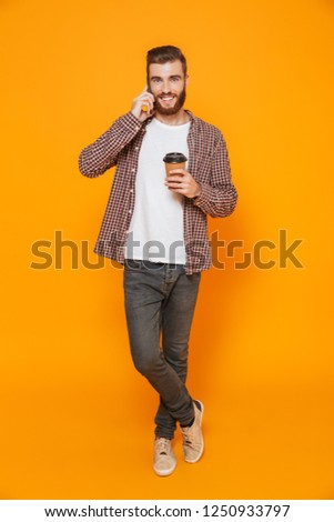 Full length portrait of a cheerful young man wearing casual clothes isolated over yellow background, holding takeaway coffee cup, talking on mobile phone #1250933797