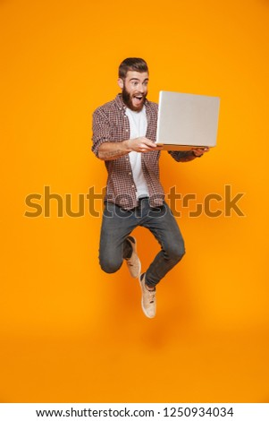 Full length portrait of a cheerful young man wearing casual clothes isolated over yellow background, holding laptop computer, jumping