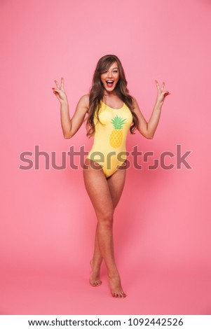 Full length portrait of a cheerful young woman dressed in swimsuit posing while showing peace gesture isolated over pink background - Shutterstock ID 1092442526