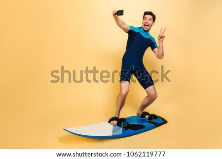 Full length portrait of a cheery young man dressed in swimsuit taking a selfie while surfing on a board isolated over yellow background