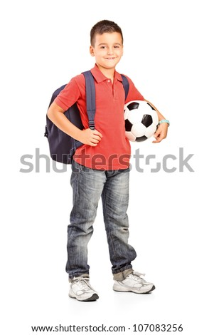 Full length portrait of a child with backpack holding a soccer ball isolated on white background