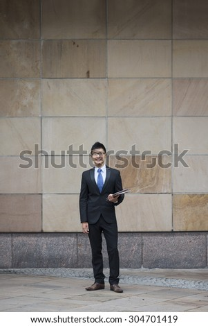 Full length Portrait of a Chinese businessman outside modern office building. Asian businessman smiling & looking at the camera.
