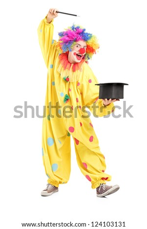 Full length portrait of a circus clown performing a magic trick isolated on white background