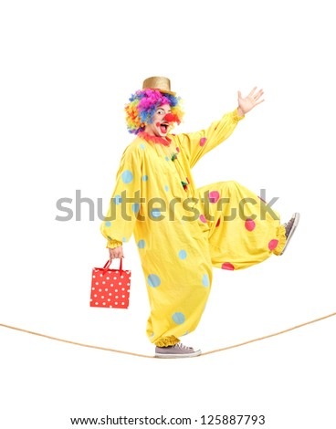 Full length portrait of a clown holding a bag and walking on a rope isolated on white background