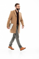 Full length portrait of a confident bearded guy dressed in coat holding laptop computer while walking isolated over white background