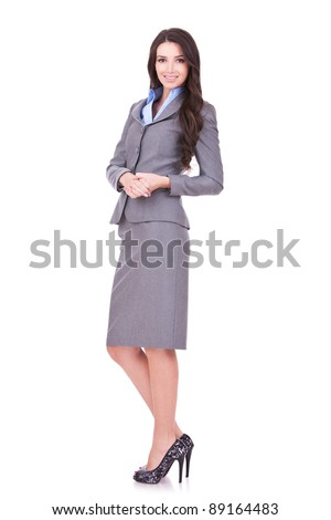 Full length portrait of a confident young business woman standing on white background