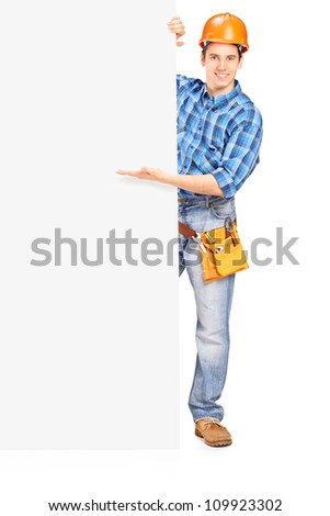 Full length portrait of a construction worker with helmet posing behind a blank panel isolated on white
