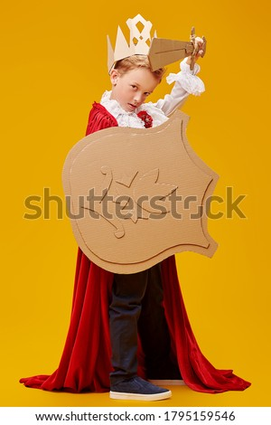 Full length portrait of a cute brave boy in a knight costume with cardboard armour. Yellow background. Childhood dreams and fantasy. Carnival, Theater. Stock photo ©