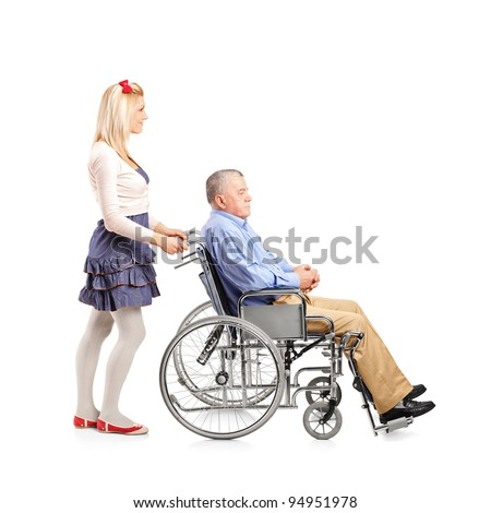 Full length portrait of a daughter pushing her dad in a wheelchair isolated on white background