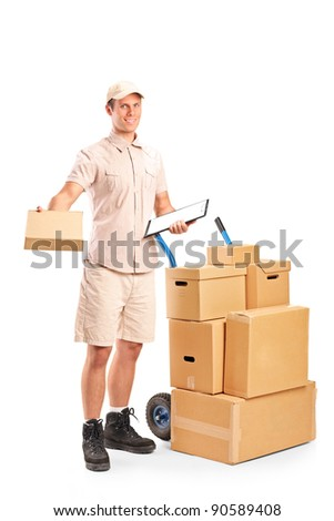 Full length portrait of a delivery boy holding a clipboard posing next to a hand truck with stack of boxes isolated on white background