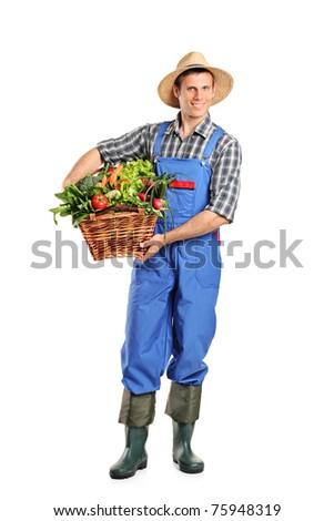 Full length portrait of a farmer holding a basket full of vegetables isolated on white background