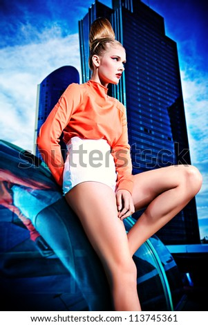 Full length portrait of a fashion model posing over big city background.