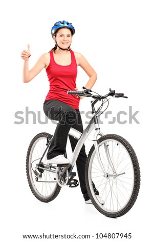 Full length portrait of a female bicyclist posing on a bicycle and giving a thumb up isolated against white background