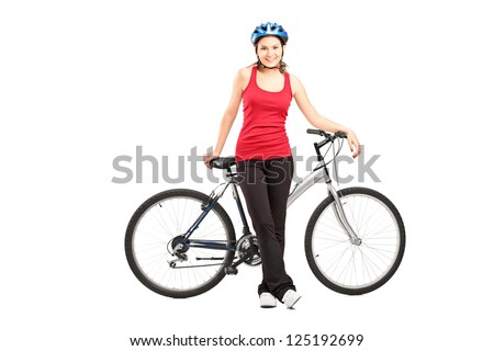 Full length portrait of a female biker with helmet posing next to a mountain bike isolated against white background