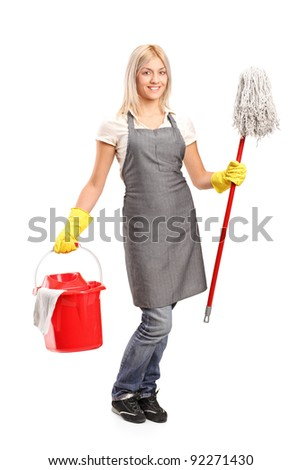 Full length portrait of a female cleaner holding a bucket with cleaning supplies and and floor cleaner isolated on white background