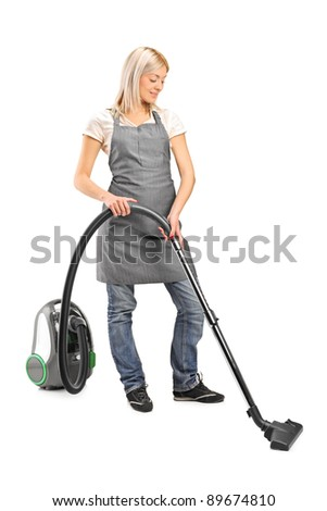 Full length portrait of a female cleaning with vacuum cleaner isolated on white background