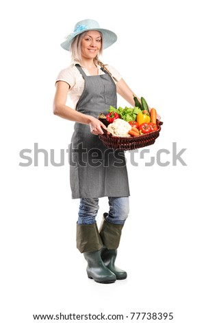 Full length portrait of a female farmer holding a basket of vegetables isolated on white background