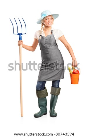 Full length portrait of a female farmer holding a pitchfork and bucket with vegetables isolated on white background