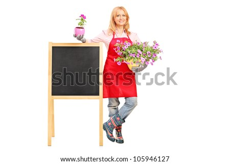 Full length portrait of a female florist holding flowers and posing next to a board isolated on white background