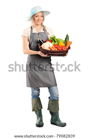 Full length portrait of a female gardener holding a basket of vegetables isolated on white background
