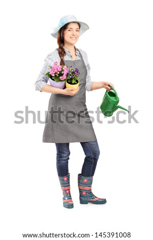 Full length portrait of a female gardener holding flower pots and watering can isolated on white background
