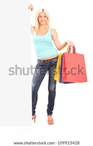 Full length portrait of a female holding shopping bags and standing next to a white panel