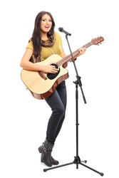 Full length portrait of a female signer playing on acoustic guitar and singing on a microphone isolated on white background