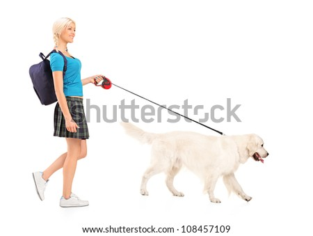 Full length portrait of a female student walking a dog, isolated on white background
