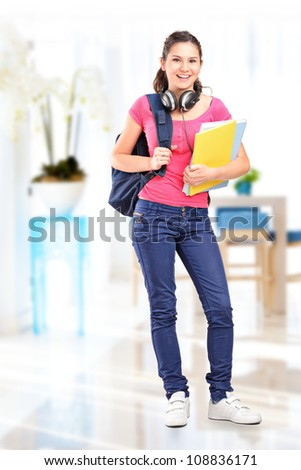 Full length portrait of a female student with headphones posing