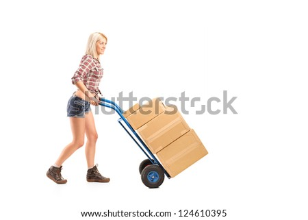 Full length portrait of a female worker pushing a hand truck with boxes isolated on white background