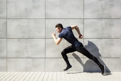 Full length portrait of a fitness man running on the street. Striving for victory.