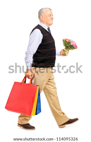 Full length portrait of a gentleman carrying gifts and bouquet isolated on white background