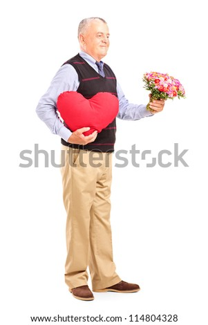 Full length portrait of a gentleman holding a red heart and flowers isolated on white background