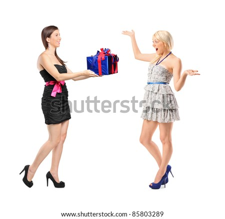 Full length portrait of a girl holding a gift and surprised woman isolated on white background