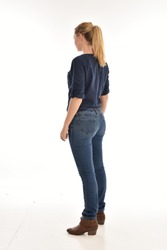 Full length portrait of a girl wearing simple blue shirt and jeans, standing pose facing away on a white background.