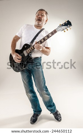 Full length portrait of a guitar player exciting music on gray background