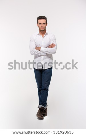 Full length portrait of a handsome man standing with arms folded isolated on a white background #331920635
