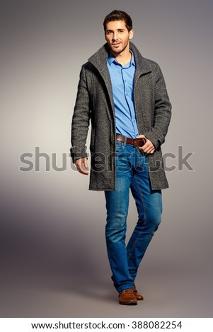 Full length portrait of a handsome man wearing jeans clothes and a coat. Men\'s beauty, seasonal fashion. Studio shot.