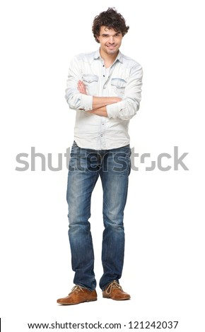 Full length portrait of a handsome young man crossing his arms and smiling. Isolated on white background